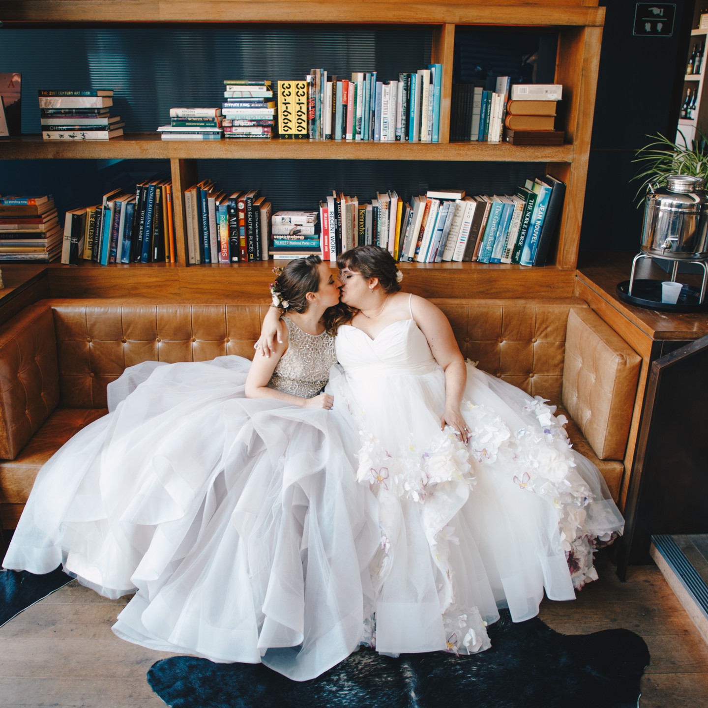 Wide shot of a library-like space with a large leather brown comfy couch that is holding our brides who sit side by side, the one with the white dress has her arm around the one with the champagne dress; their eyes are closed and they may be thinking how perfect a space since books are part of their story.