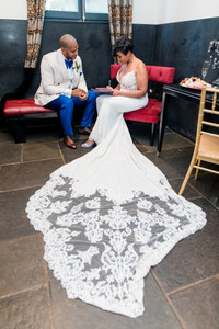 Bride and groom signing their marriage license while sitting down on red-cushioned chairs, the brides dress train and veil are spread widely for a dramatic appearance