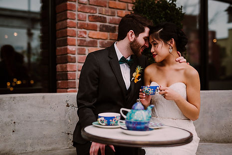 Interracial couple having tea at The Williamsburg Hotel while the groom touches the bride's neck in a tender moment.