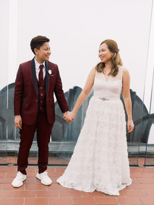 At Top of the Rock, two Asian brides standing side by side holding hands and looking at each other; masculine presenting bride is wearing wine red three piece suit and tie with white collared shirt and white sneakers and femme presenting bride wearing white dress with a semi updo hair style.