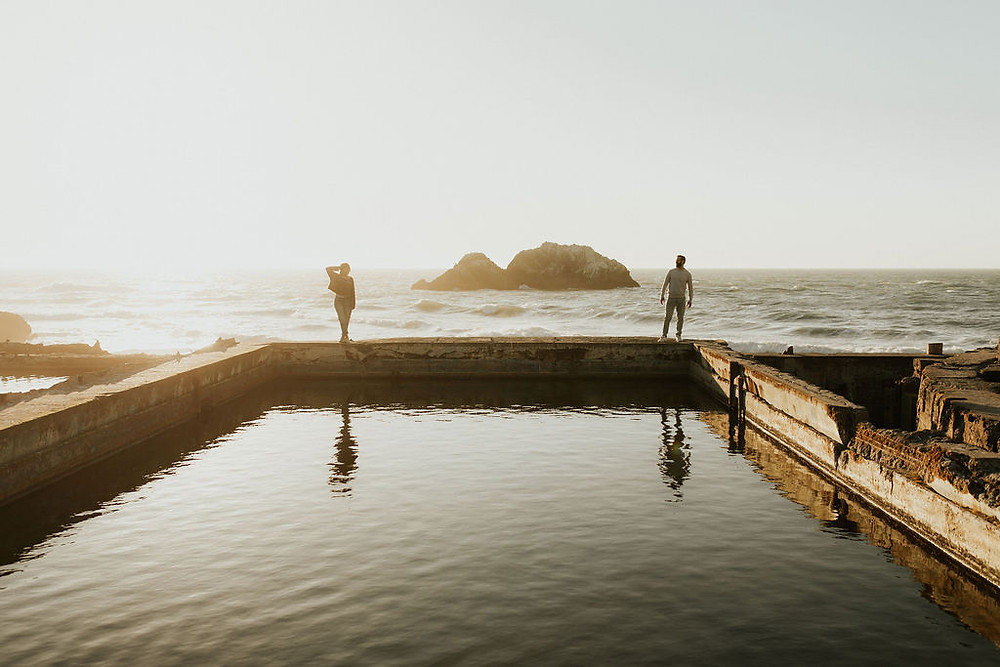 A couple at Sutro Baths in San Francisco, CA standing far from each other with the beach, the ocean, and rock formation behind them, one is an officiant from Once Upon A Vow