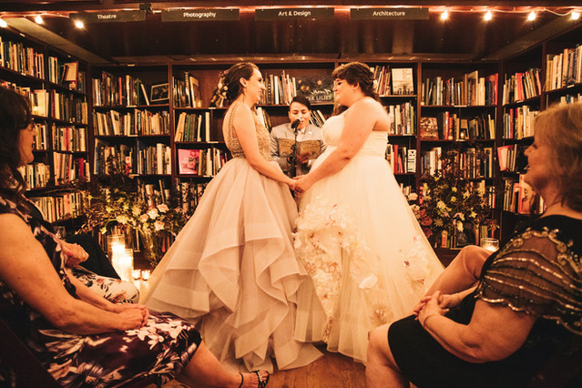 Two brides holding hands and looking at each other lovingly with queer officiant from Once Upon A Vow reading welcoming them and their guests to HousingWorks; the lighting is intimate and romantically dim with candles lit beside each of them and shelves full of books all around them.
