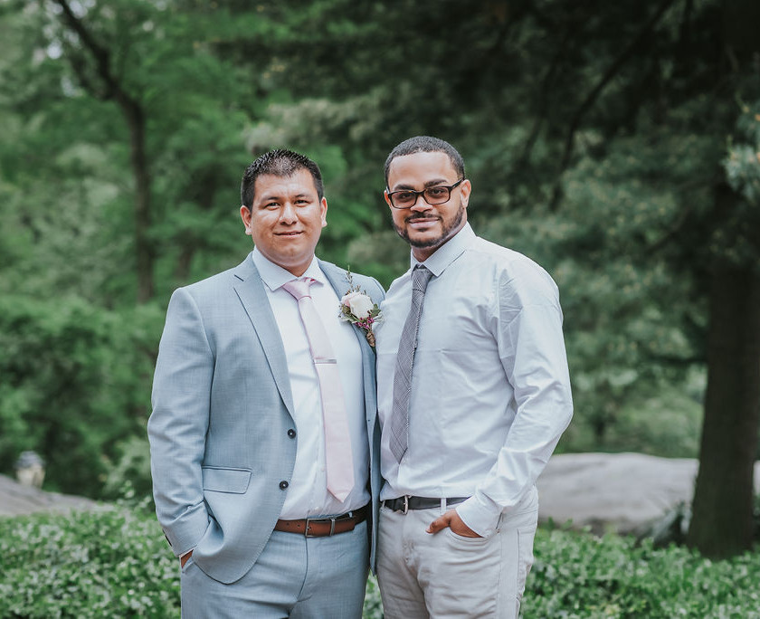 Photo of groom dressed in a light blue suit with a soft pink tie standing next to his groomsman while standing right outside of Central Park's Cop Cot before the ceremony begins officiated by bilingual officiant from Once Upon A Vow