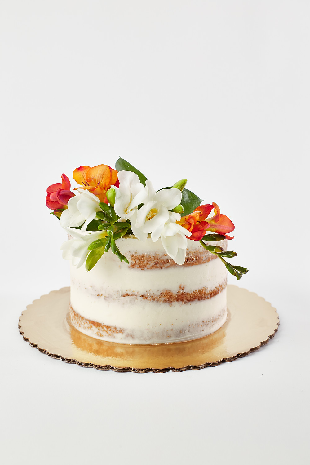 Photo of a naked cake with vanilla icing and floral top with white and orange florals from Park Slope's Buttermilk Bakeshop
