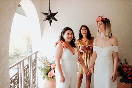 Photo of ceremony focused on two smiling brides looking at each other and the happy officiant from Once Upon A Vow; brides are holding hands throughout the ceremony.