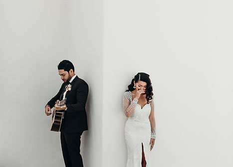 A white background focusing on a couple doing their first look; the groom strums the guitar while the bride cries from the emotional songs he is playing.