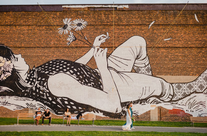 Photo from a distance of woman laying down holding daises mural in Greenpoint's Transmitter Park while newly married couple walks forward, towards the right of the photo and NYC dwellers sit on a bench behind them, in the left-hand frame