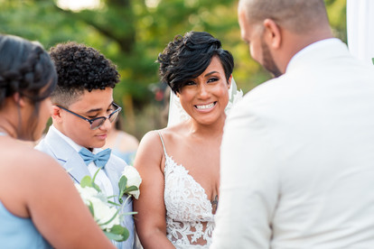 Overlooking groom's left shoulder, and focus on smiling and crying bride during the ring warming of the bilingual wedding ceremony officiated by Once Upon A Vow