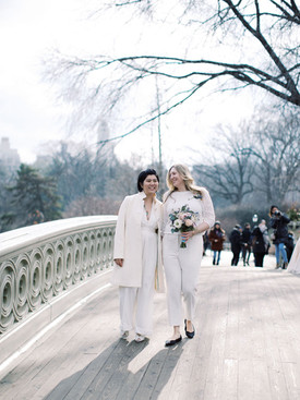 Two brides in their white wedding pants outfits walking along Bow Bridge; the Asian-Canadian bride is wearing her off-white winter coat and the Anglo-American bride is carrying her bouquet; picture taken post elopement ceremony officiated by lgbtq+ officiant at Once Upon A Vow.