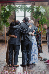 Close-up photo of group hug between parents and the soon-to-be newlyweds while one groomsman is seen clapping hands and the officiant from Once Upon A Vow is smiling in the background, set in Brooklyn's Greenpoint Loft