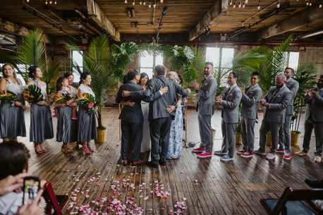 Wide photo of the group hug after the ring warming portion of the ceremony led by modern officiant from Once Upon A Vow; groomsmen are clapping and bridesmaids are smiling, one guest on the lower left corner seems to be taking a photo in Brooklyn's Greenpoint Loft