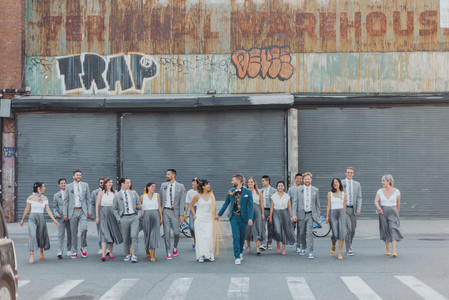 Wide group photo with the couple in the center and their wedding party behind them as they walk towards the camera in Greenpoint Brooklyn
