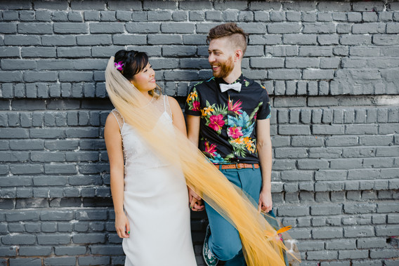Newlyweds leaning on this grey brick background smiling and looking at each other while the bride's ombre yellow veil horizontally crosses them both