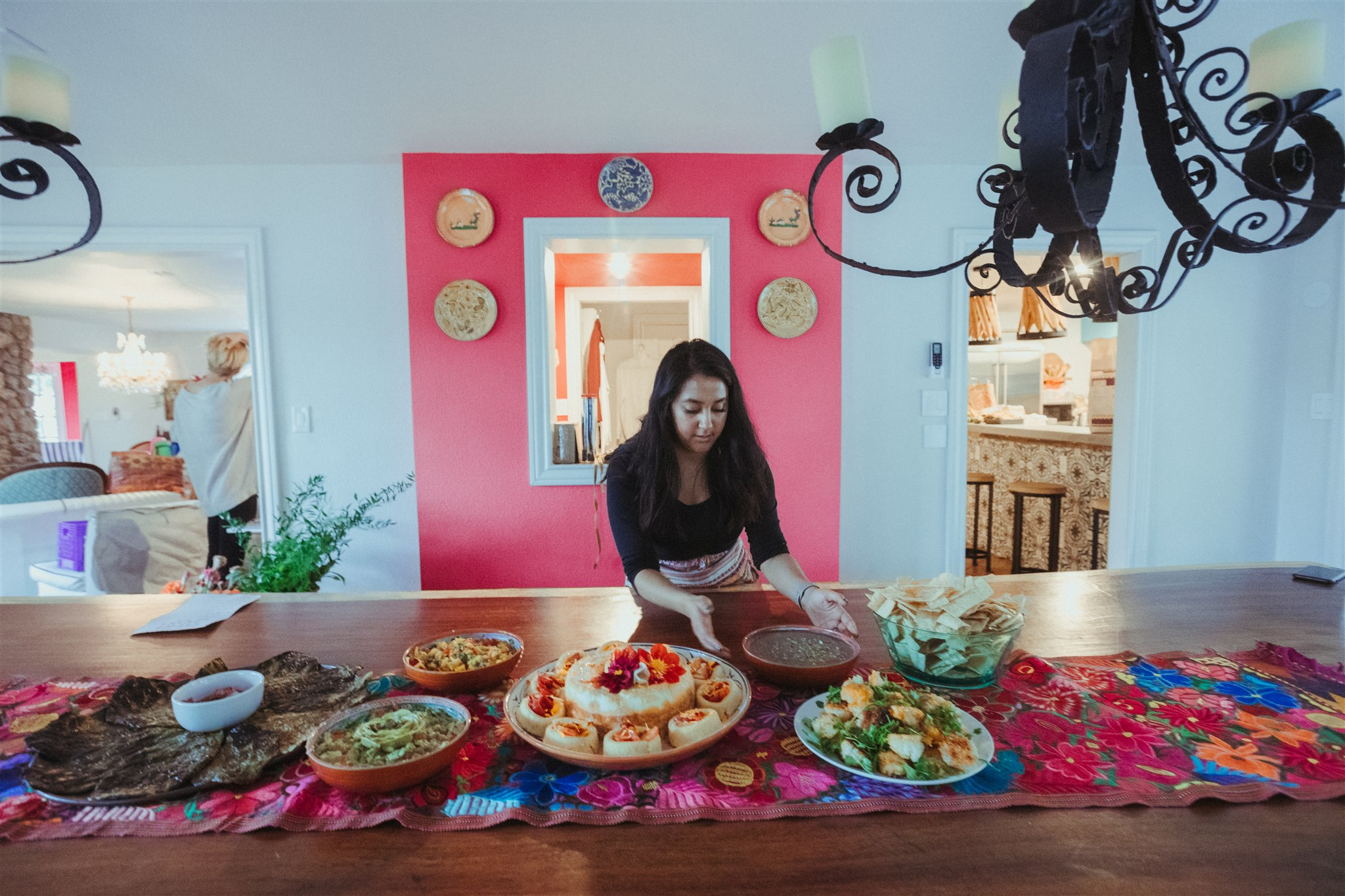 Mary-Beth from Heart of Celebrations setting the table with delicious flavorful Latinx dishes on a deep wood table with a floral Guatemalan table runner and a pink focal wall with colorful plates on it