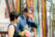 Brooklyn vow renewal for 40th wedding anniversary performed by sister officiants of Once Upon A Vow, where husband is touching tearful eyes and smiling wife holds colorful bouquet with colorful fringe on iron doors as the ceremony backdrop.
