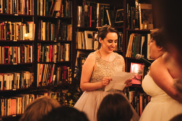 Bride in champagne dress reading her vows; she's smiling and her bride appears to be laughing; the background is of shelves of books and the shot captures a few of the guests heads.