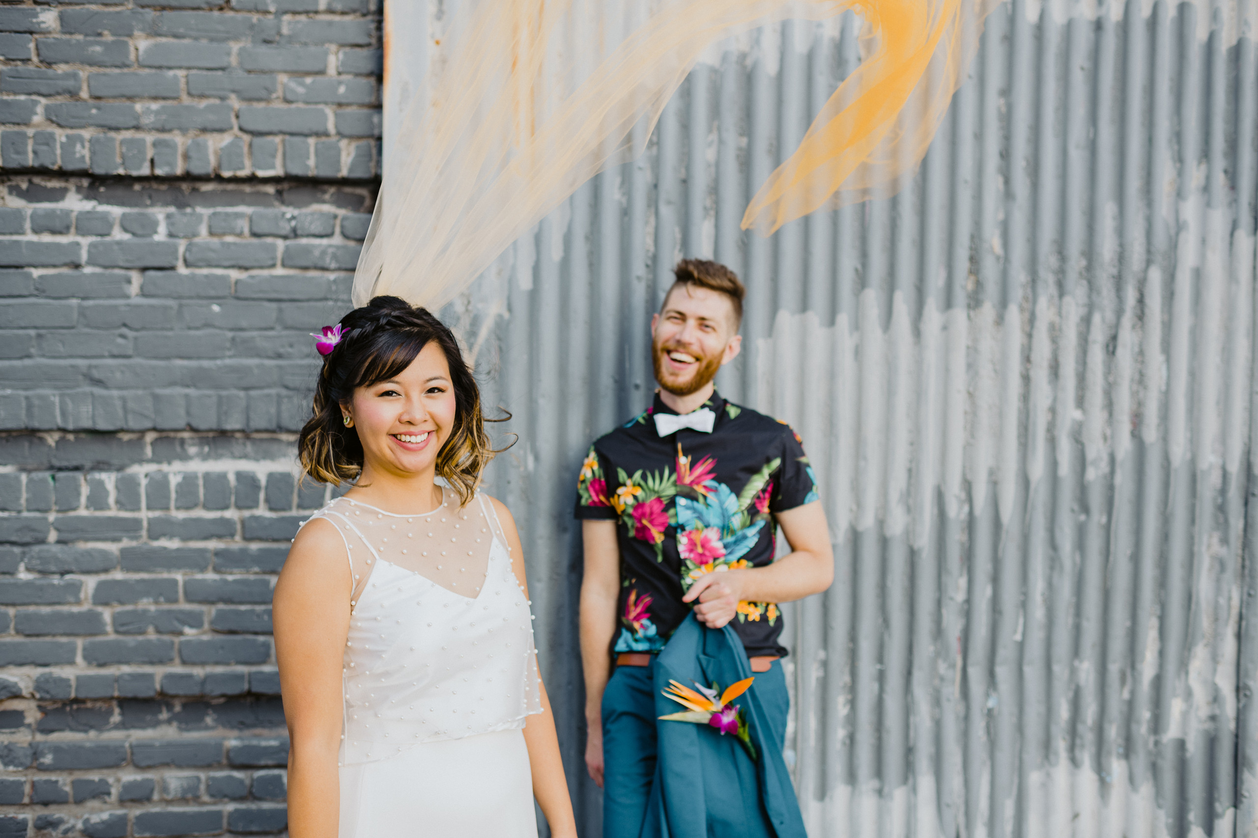 Smiling interracial couple, Chinese bride with purple floral in her braided hair and ombre yellow veil floating mid-air that's swooping towards with anglo-american groom wearing a black tropical collared shirt with bright pink and teal details and white bowtie against a grey brick background in Greenpoint Brooklyn