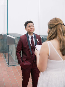 At the Top of the Rock, a shot of masculine presenting bride reacting to her beloved's reading of her vows; she appears to be holding back tears.