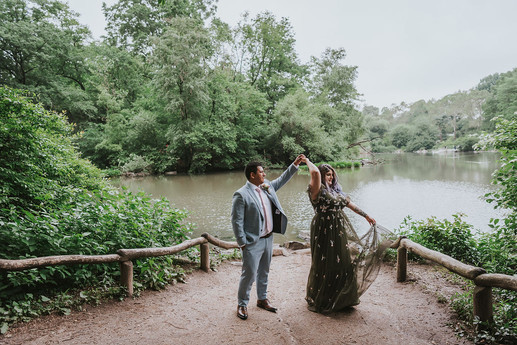 Candid photo of bride and groom dancing, bride is in mid-twirl and her tulle olive dress is seen through, the background is the Central Park pond with trees and greenery surrounding the area