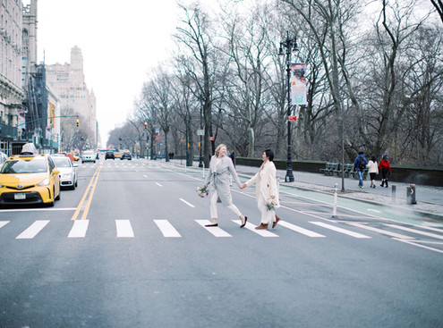 Two brides walking hand in hand across the 72nd street Fifth avenue crosswalk with bouquets in hand and coats on on their way to catch a cab; yellow cab and other cars in the background.