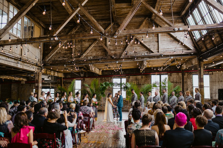Wide photo of the fun colorful ceremony in Greenpoint Loft with the couple and officiant from Once Upon A Vow at the center, bridesmaids to the left, groomsmen to the right, and the back of guests' heads some of whom are taking photos