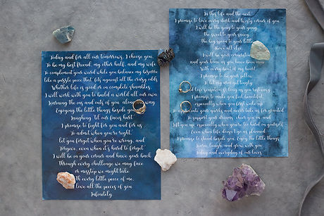 Flatlay of wedding vow calligraphy set in a indigo blue wash with wedding rings and crystals surrounding it