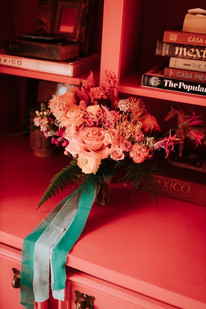 Photo of lush pink floral bouquet set upon a pink desk with books with shelves holding books.