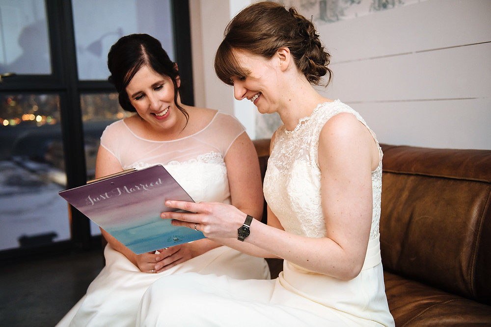 Photo of two newly married brides smiling and looking down at an ombre pink to teal clipboard that says 'Just Married' that holds their just-signed marriage license after their ceremony officiated by modern LGBTQ inclusive officiant from Once Upon A Vow