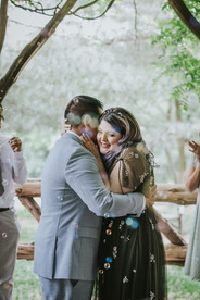 Close up photo of the smiling bride embracing her husband as bubbles and rainbow-colored orbs surround them post-ceremony officiated by Spanish-speaking officiant from Once Upon A Vow
