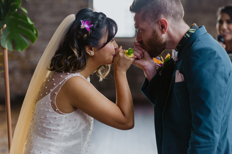 Photo of couple doing a pinky promise kiss while wearing the ring pops, interlocking pinky fingers and kissing their own thumbs led by fun and unique wedding officiant from Once Upon A Vow in Greenpoint Loft, Brooklyn