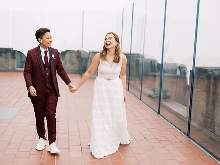 LGBTQ couple, one in burgundy suit and white sneakers and the other in white dress get married at the Top of the Rock elopement in New York City with queer officiant from Once Upon A Vow