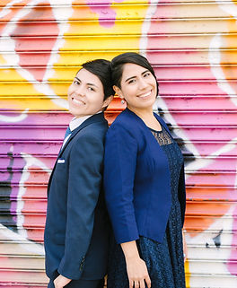 Smiling bilingual spanish and english speaking wedding officiants standing back-to-back with a colorful mural background in Brooklyn, NY