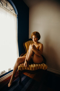 Boudoir photo shoot with black model staring into the camera, sitting on a vintage mustard chair next to a draped well lit window