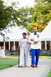 Groom in royal blue suit pants, velvet blue tie, and double-breasted white blazer walks down the aisle escorted by mother of the groom in silver dress