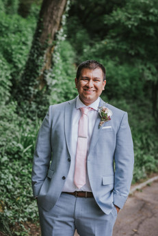 Portrait of groom smiling at the camera while wearing the blue suit with light pink tie and boutonniere set among a lush greenery background in Central Park