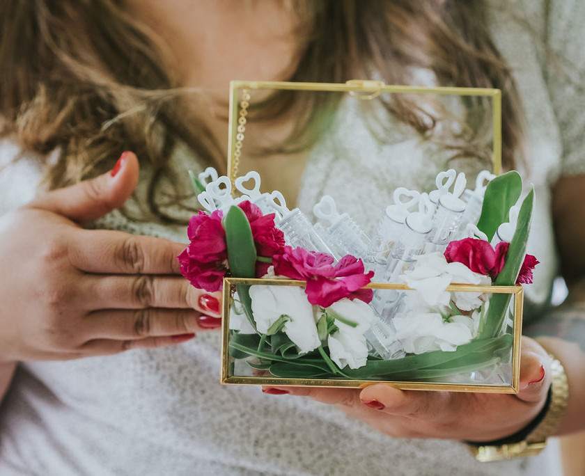 Detail close-up photo of a clear box with gold trim which holds tubes of bubbles with florals held by a woman wearing white with red nails before the Central Park elopement officiated by Spanish speaking officiant from Once Upon A Vow