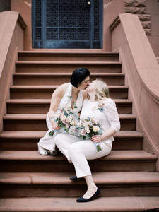 Two brides on Upper West side brownstone steps; they're holding their bouquets and sharing a smooch; picture taken post elopement ceremony officiated by lesbian officiant at Once Upon A Vow.