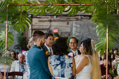 Photo of ring warming ritual taken behind the Brooklyn wedding officiant from Once Upon A Vow framed by tropical ceremony backdrop blending two families together in Brooklyn's Greenpoint Loft