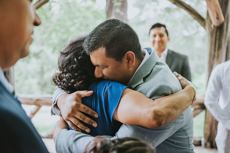 Close-up photo of groom hugging his mother dressed in blue in the center of Central Park's Cop Cot post-ceremony led by Spanish-speaking NYC wedding officiant from Once Upon A Vow