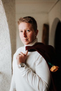 Portrait of one LGBTQ newlywed standing in a spanish-style hallway wearing a cream turtleneck and holding the maroon blazer across left shoulder with one finger, light eyes pierce looking past the camera.