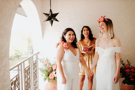 Intimate wedding ceremony at Casa Cartel with modern, feminist officiant dressed in yellow from Once Upon A Vow marrying two brides, one in a white jumpsuit with floral shoulder and the other bride with off the shoulder white dress and floral crown