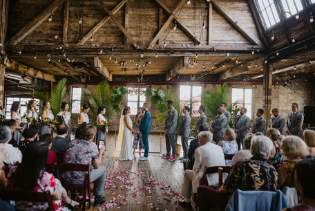 Wide photo of ceremony with the couple and fun officiant from Once Upon A Vow at the center and some guests leaning in to take photos with a floral aisle and lovely wooden beam details of the Greenpoint Loft