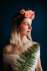 Peaceful blonde bride portrait looking out into the natural light wearing a pink floral crown and holding a tropical looking leaf across her chest.