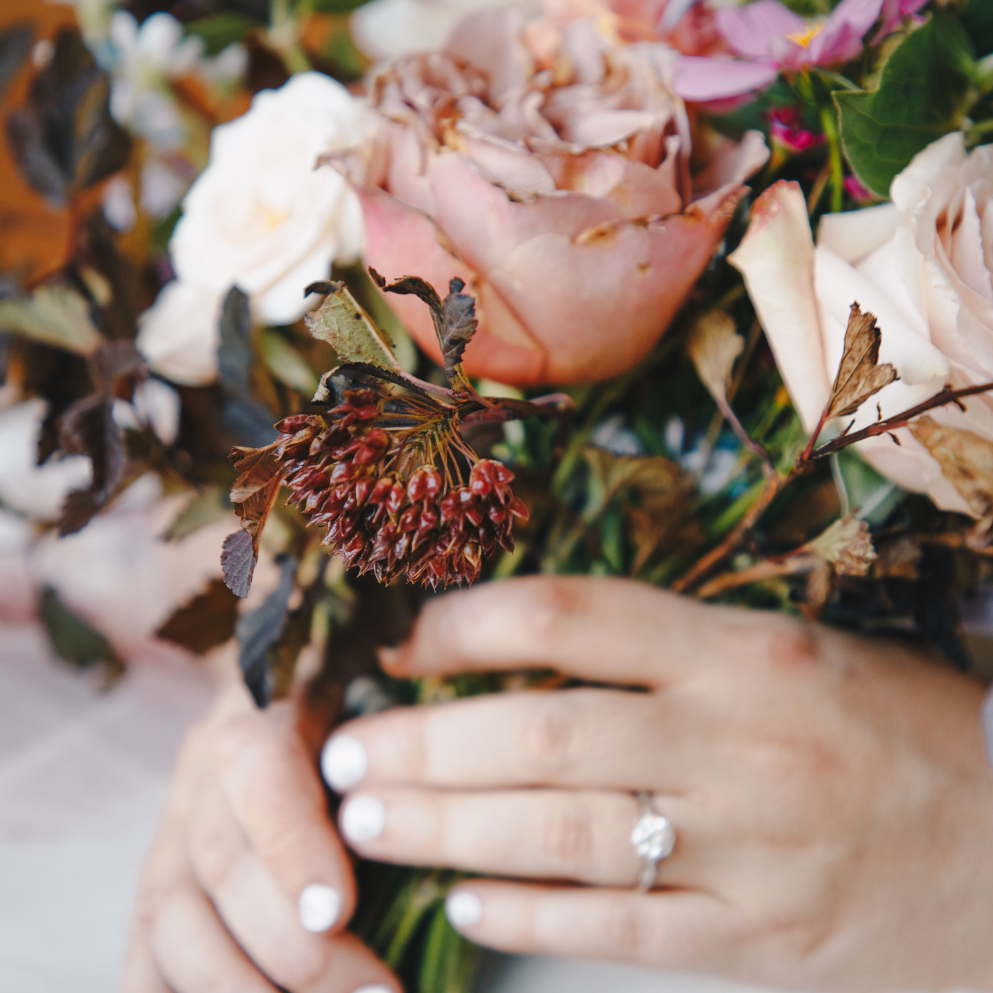Close up shot of bouquet and hands of caucasian bride; beautiful diamond engagement ring on full display.