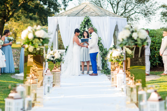 Landscape shot of ceremony centering bride and groom holding hands during the bilingual wedding ceremony officiated by Once Upon A Vow at Pelham Bay Golf Course's gazebo
