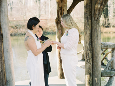 Asian-Canadian bride placing the wedding ring on the Anglo-American bride who is smiling as she listens to her partner's vows with queer officiant from Once Upon A Vow guiding them along.