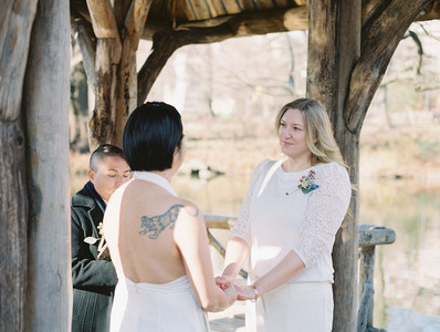Asian-Canadian and Anglo-American brides holding hands and looking at each other lovingly at Wagner's Cove, one in a halter-top jumpsuit and the other in nice pants and a sweater blouse as their queer officiant from Once Upon A Vow shares their love story.