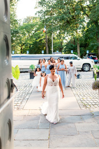 Beautiful bride smiling and walking towards the camera with v-neck lace top wedding dress with mother of the bride, bridesmaids and flower girls walking behind her and limo in the background.