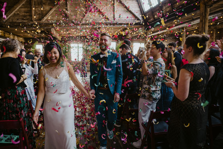 Photo of bride and groom laughing as they are surrounded by colorful confetti post-ceremony officiated by Once Upon A Vow in Greenpoint Loft, Brooklyn