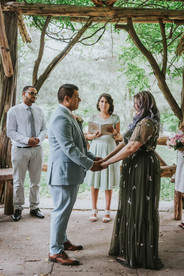 Photo of the Spanish ceremony officiated by modern elopement officiant from Once Upon A Vow at the center with the groom in the left frame and the bride on the right holding hands staring at one another as they are surrounded by their bridesmaids and groomsmen in Central Park's Cop Cot